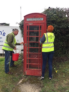 Image two people cleaning red phone box